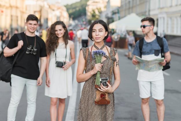 友人と街を探索する花とカメラを持つ女性