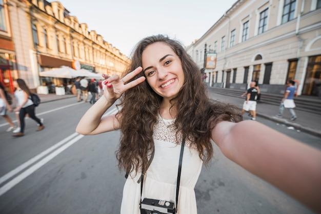 Молодая женщина показывает знак мира