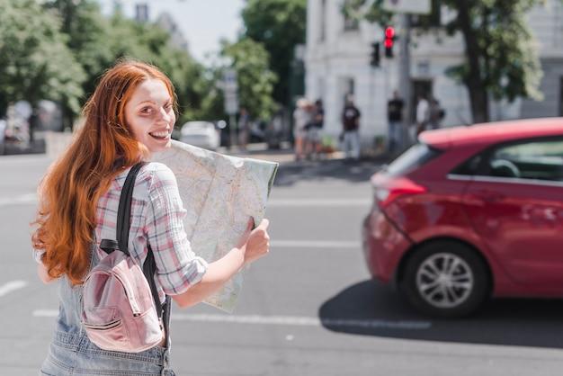 都市の地図で通りに立っている女性