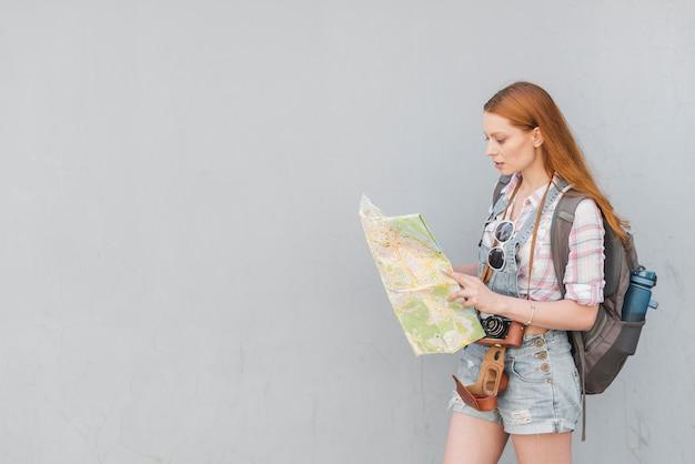 バックパックと地図で歩く女性