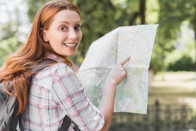 地図を指しているかわいい女性