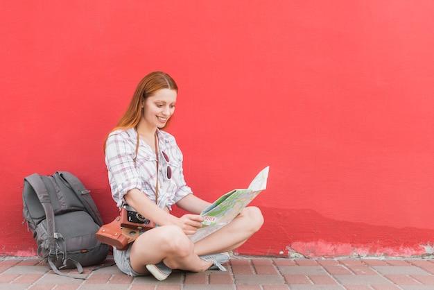 壁の近くに座っている旅行者の読書街の地図