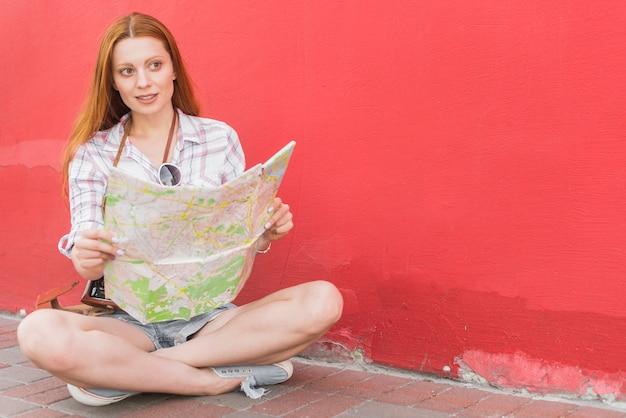 壁の近くの地面に座っている地図で女性