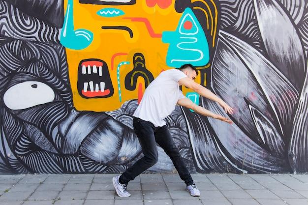 落書きの壁の前で踊るヒップホッパー