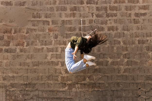 フレキシブルなモダンなスタイルの女性ダンサー、空気中でジャンプ