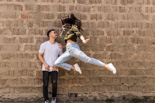 ジャンプする女性のダンサーを見て笑顔の男