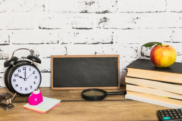 Доска и школьные принадлежности с яблоком на вершине книг
