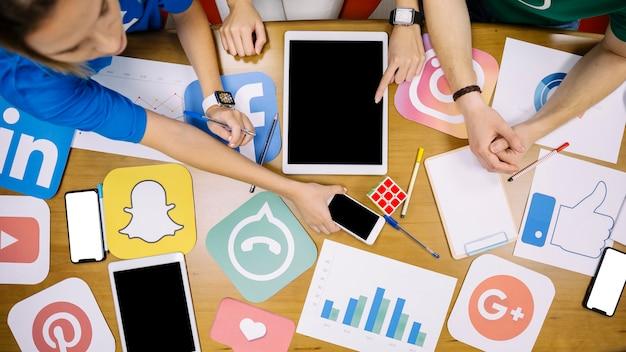 Команда с иконками социальных сетей и электронным гаджетом над столом