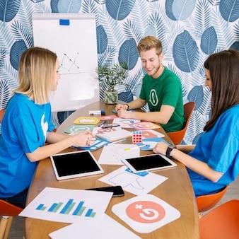 成功したチームがソーシャルメディアアプリケーションのオフィスで議論