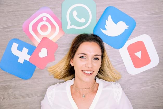 ソーシャルネットワーキングのアイコンで壁の前に立っている笑顔の女性の肖像