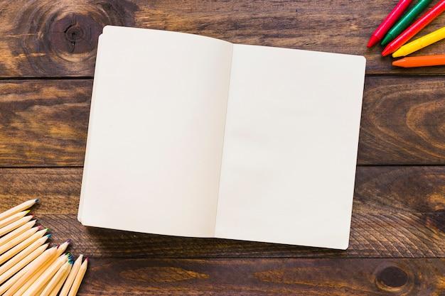 開いたノートブックの近くのクレヨンと鉛筆