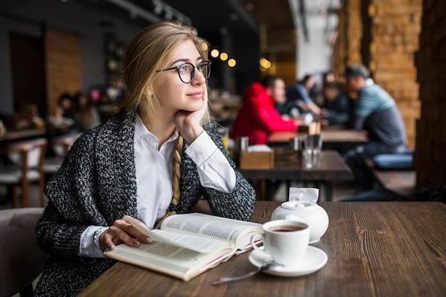 若い女性を本で夢見る