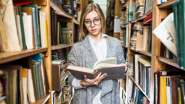 Симпатичная женщина с открытой книгой, глядя на камеру