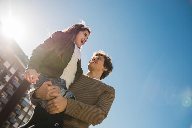 彼の娘を運ぶ幸せな父親の低い角度のビュー