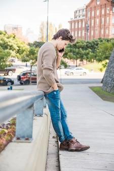 Человек, опираясь на перила во время разговора на мобильном телефоне