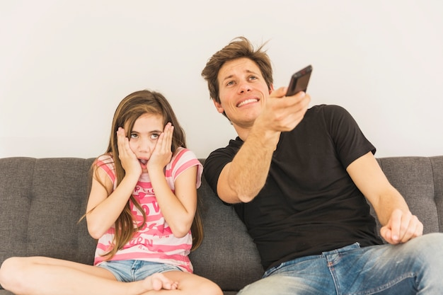 Испуганная девушка сидит с отцом, держа пульт дистанционного управления