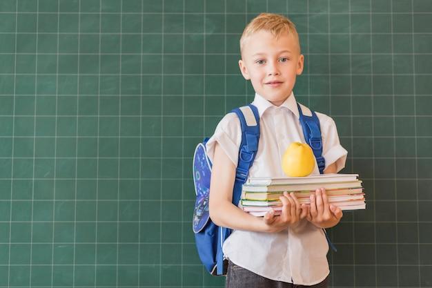 バックパックと黒板の近くの本を持つ少年