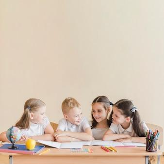 Веселые ученики, говорящие на уроке