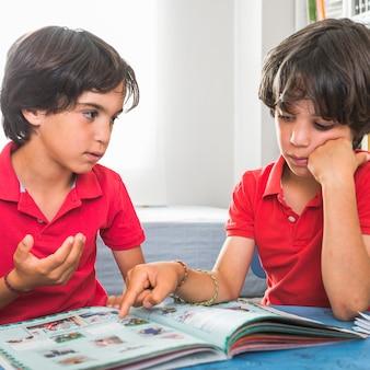 本に座って話す兄弟