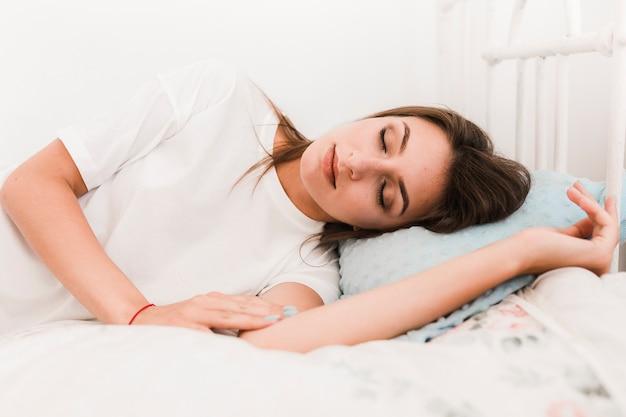 ベッドで寝るかわいい女性