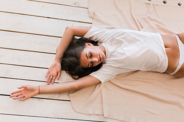 毛布に横たわっている官能的な女性