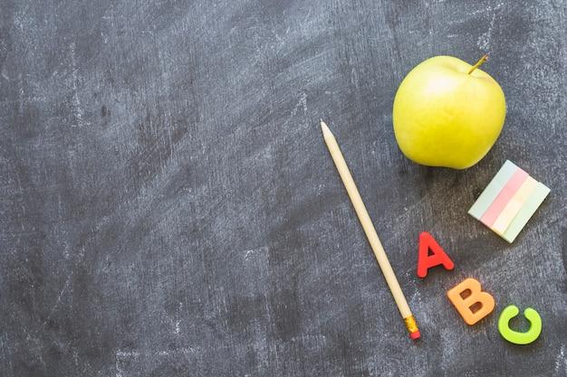 Доска с канцелярскими буквами алфавита и яблоком