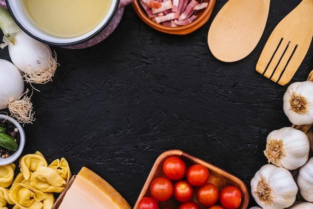 パスタの食材の近くのソースパンと食器