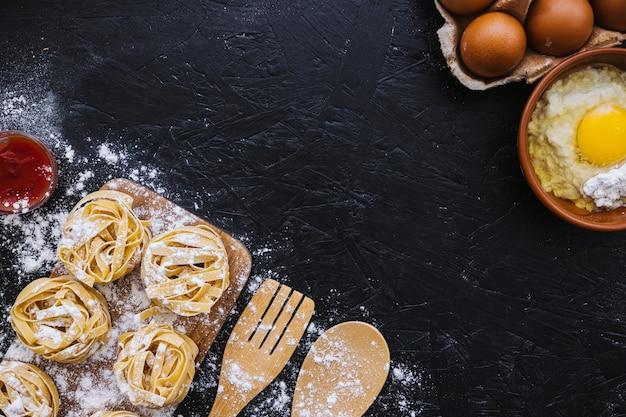 パスタや道具の近くの小麦粉と卵