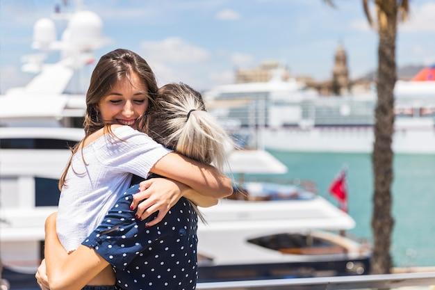 Подруги, обнимающие на берегу моря