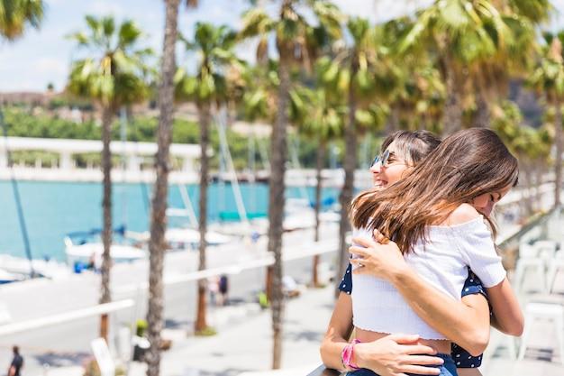 Счастливые подруги обниматься на набережной