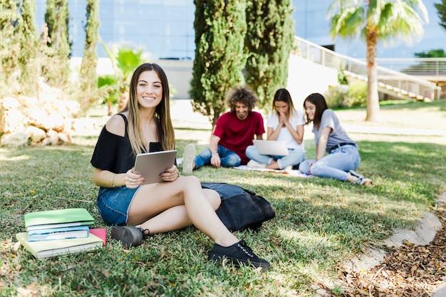外で勉強しているタブレットを持つ女性