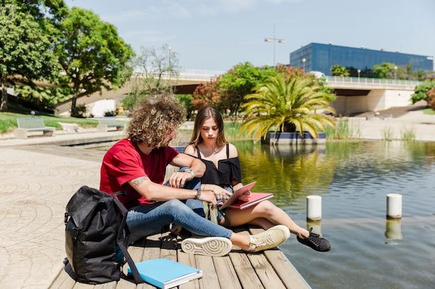 湖と公園で勉強しているカップル