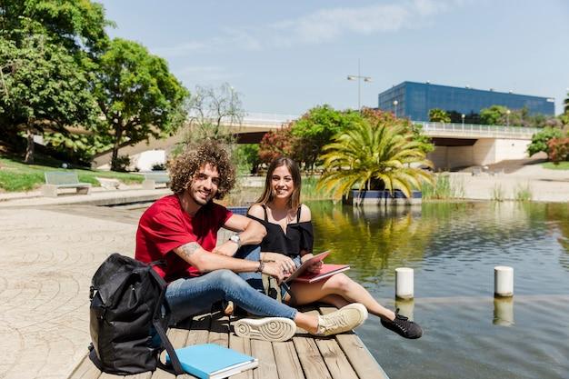 公園でのタブレットと本の学生のカップル