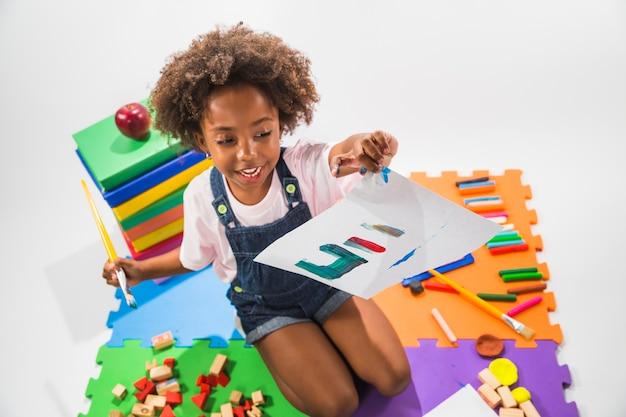 スタジオで遊びマットにペイントされた紙を持つ少女