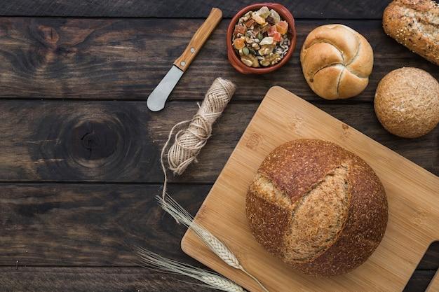 砂糖漬けの果物や道具のそばの新鮮なパン