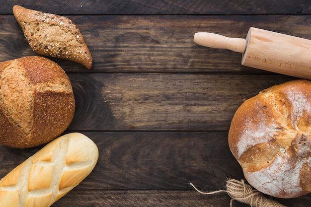 Хлеб возле скалка и нитки