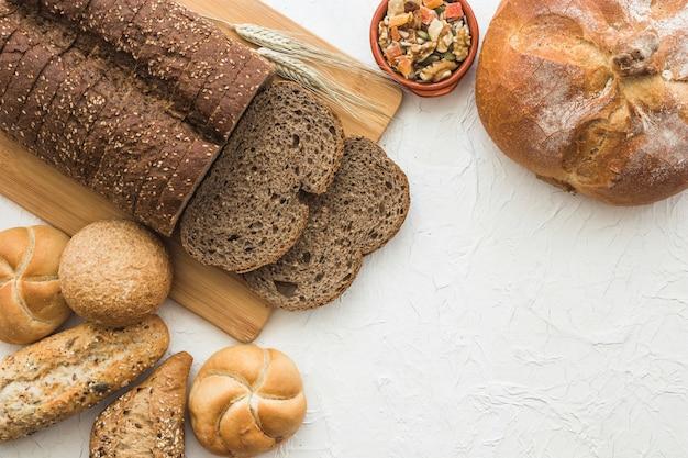 Засахаренные фрукты и орехи возле хлеба и булочек