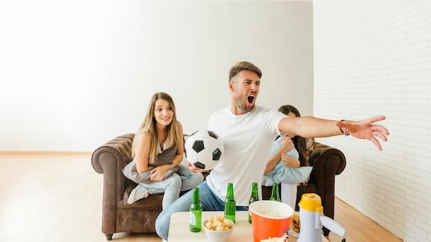 ソファで友達とサッカーの試合を見て叫ぶ男