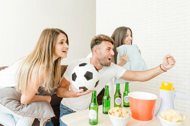 ホームでサッカーを観戦している友人たち