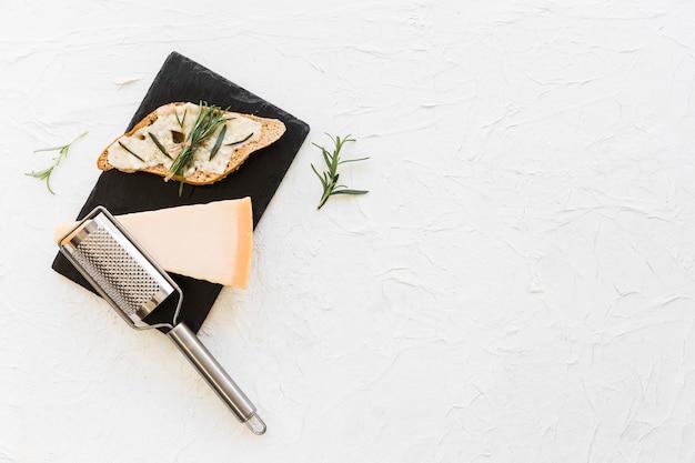 白い背景に石のプレートにチーズとローズマリーのパン