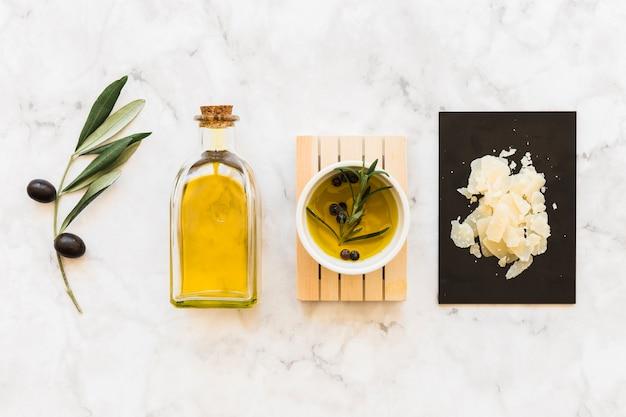 白い大理石の背景にチーズとボウルとボトルのオリーブと黒コショウ油