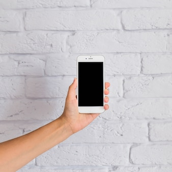 白い壁の前に空白の画面を持つ携帯電話を保持する手のクローズアップ