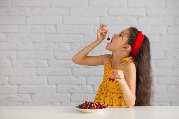 レンガの壁の前で赤い新鮮な喜びを食べる少女