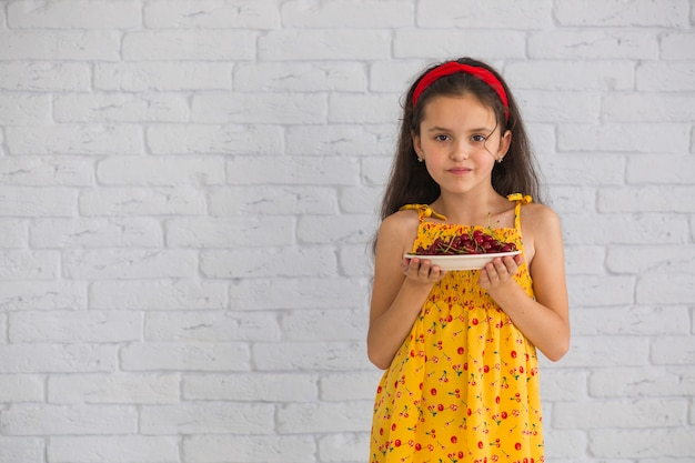 白いレンガの壁に赤いチェリーのプレートを保持している女の子の肖像