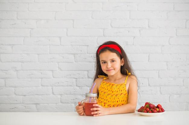 Портрет девушки, держащей клубничные коктейли в банке