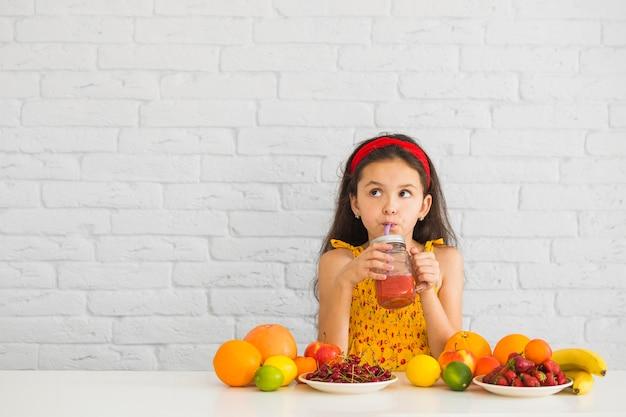机の上に色とりどりの果物とイチゴスムージーを飲む少女