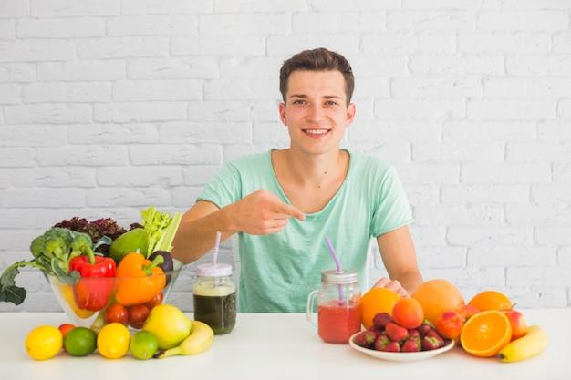 テーブル、新鮮な果物の方に指を指す男