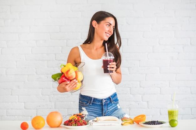 Молодая женщина, стоящих против стены, проведение чаша свежих овощей и фруктов и соков