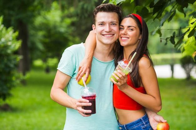 Портрет молодой пары, проведение здоровых коктейли и яблоки в парке