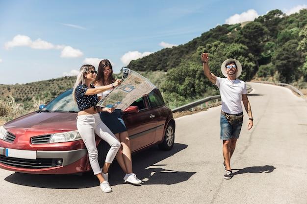 Женщины, глядя на карту, опираясь на автомобиль, в то время как ее мужской друг жестом на дороге
